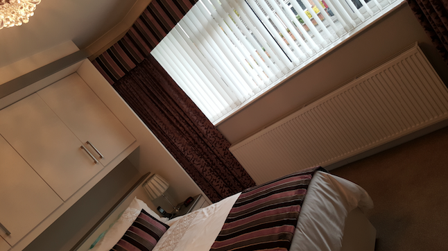 bedroom with verical blinds and curtains